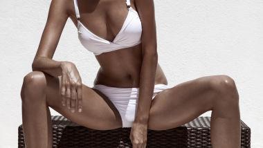 Beautiful tan female model posing in bikini and sunglasses. Against white wall.