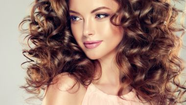 Beautiful model girl with wavy hairstyle . Brunette woman with long curly hair